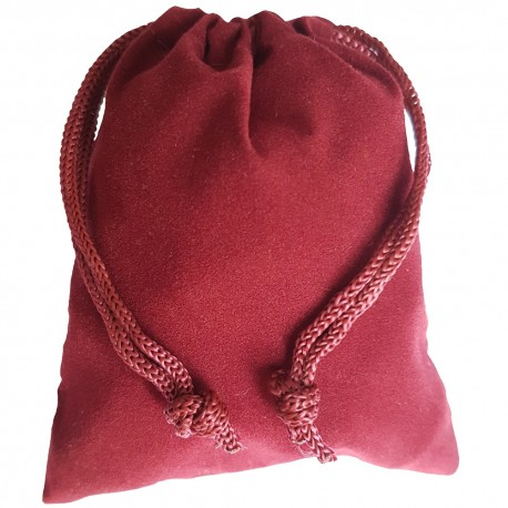 Small burgundy colored drawstring velveteen bag shown closed holding a stone rune set.