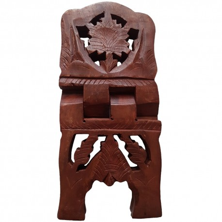 The wooden book stand has carved out designs on the arms and legs.